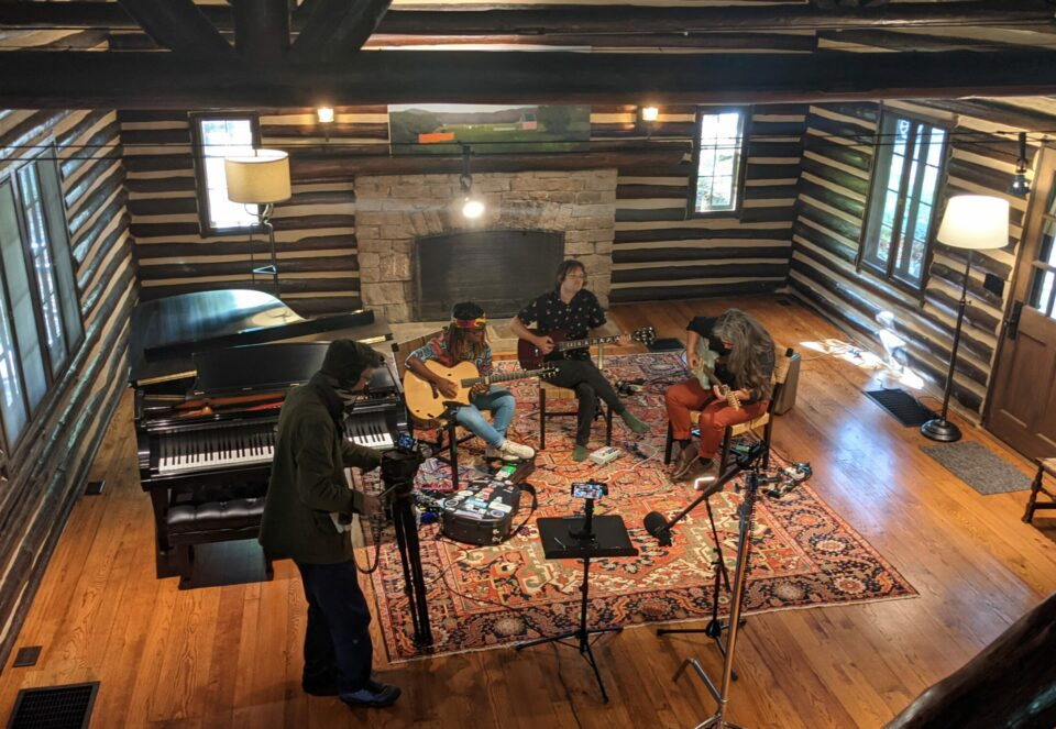 Three musicians playing guitars, one cameraman filming in a cabin